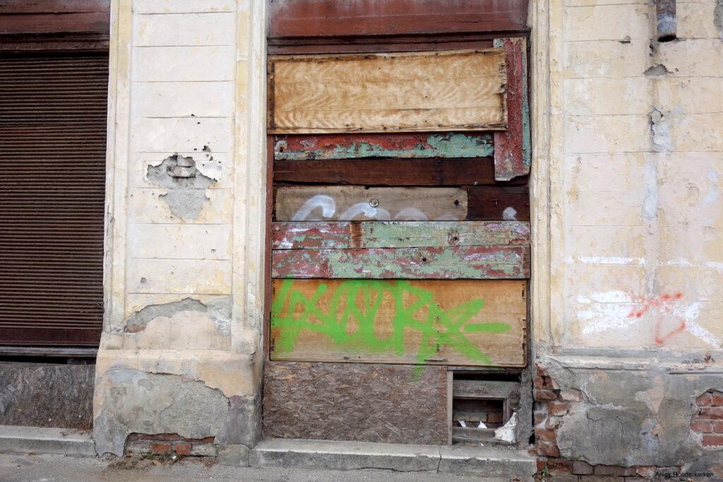 Een raam is dichtgetimmerd met kleurrijke planken, graffiti op sommige ervan. Schoonheid en verval in een foto.