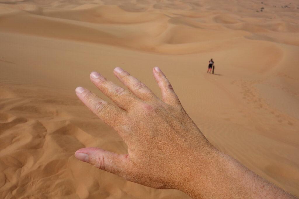 Het rode woestijnzand op mijn handen